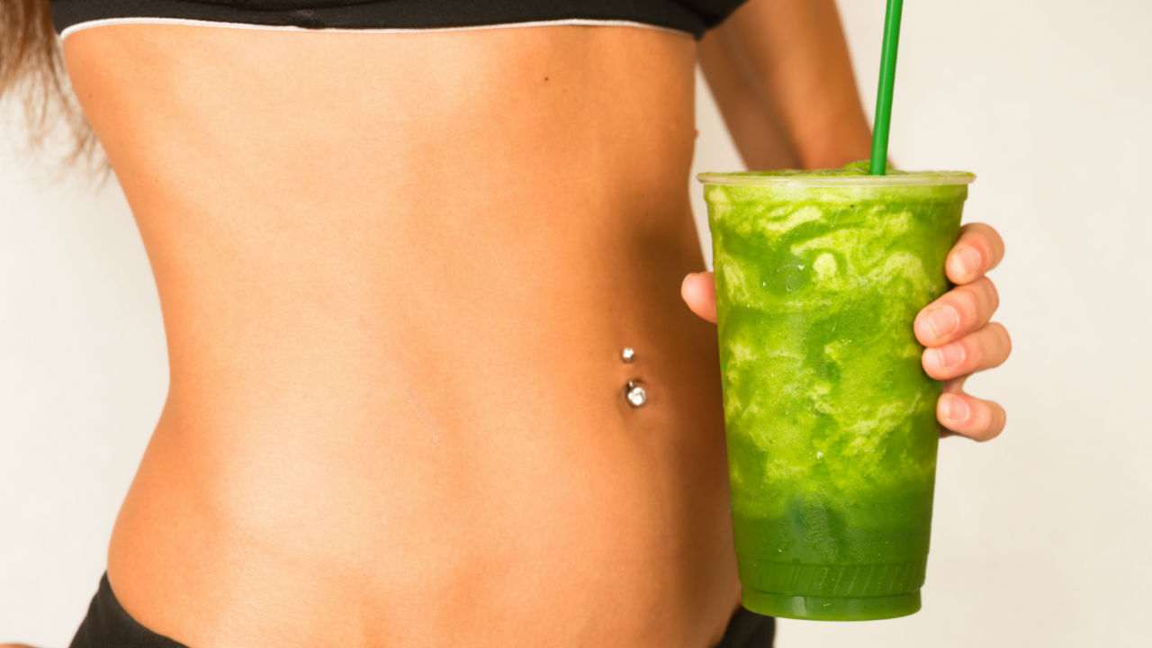women holding a green smoothie