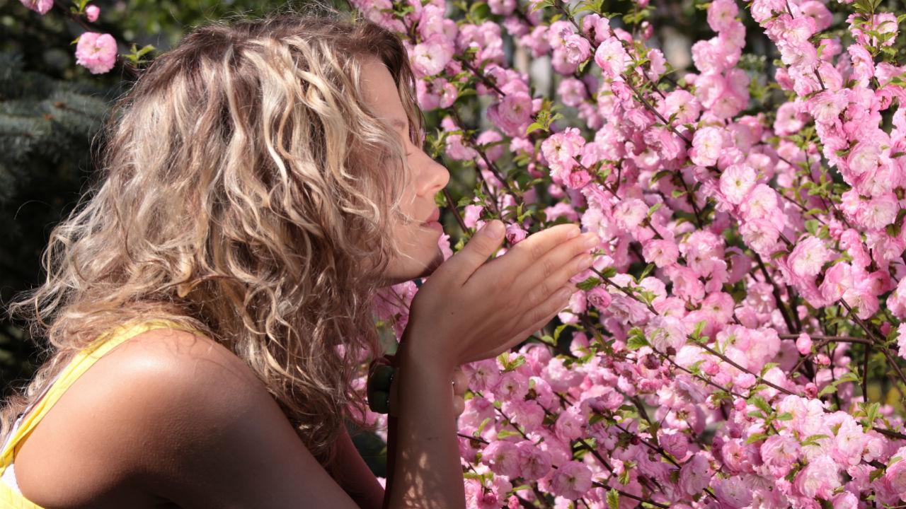 women smelling flowers