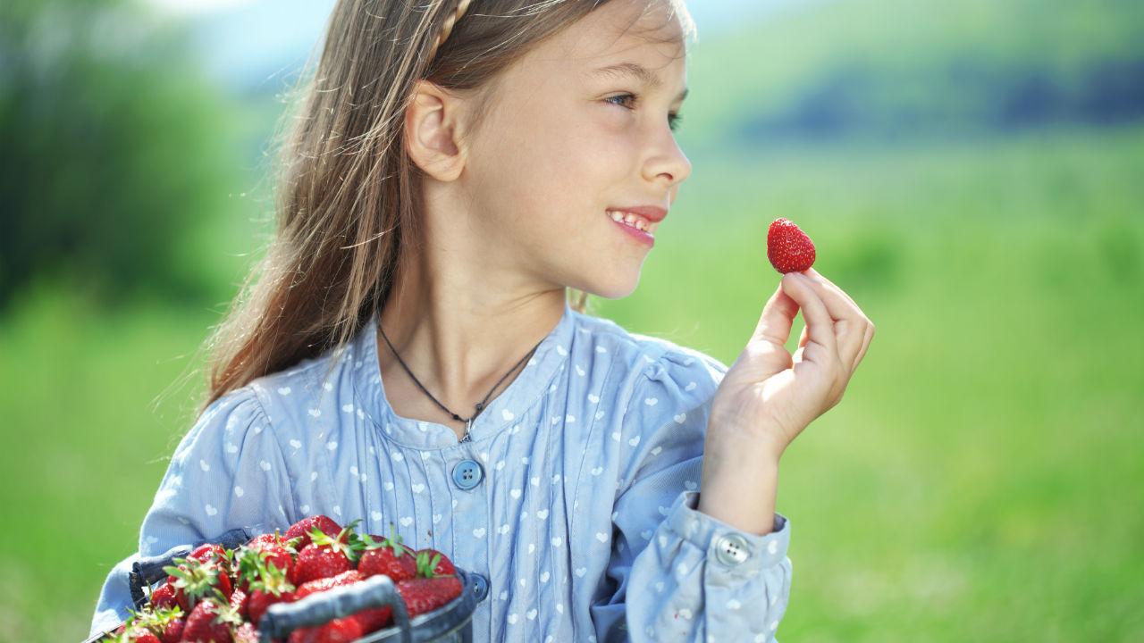 girl holding strawberries