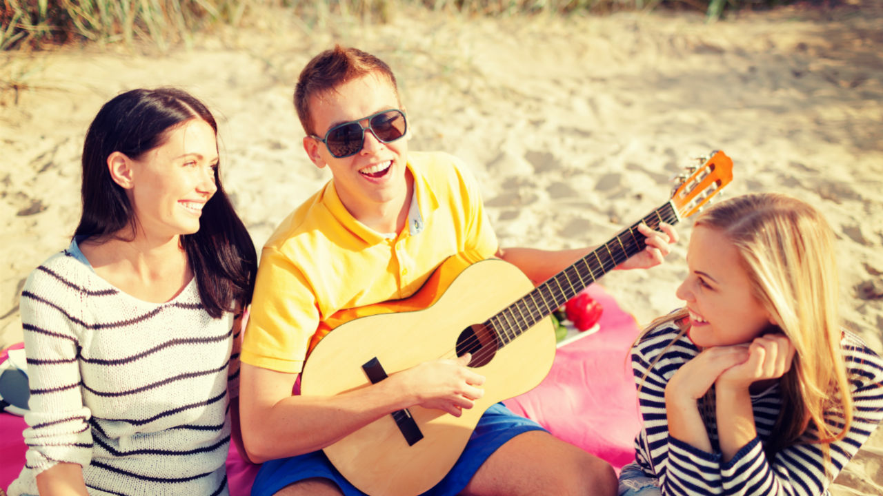 group of friends with guitar on beach
