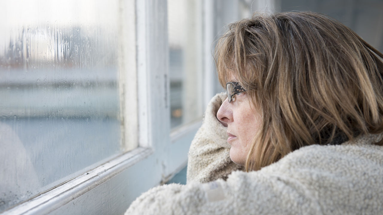 Woman looks out window