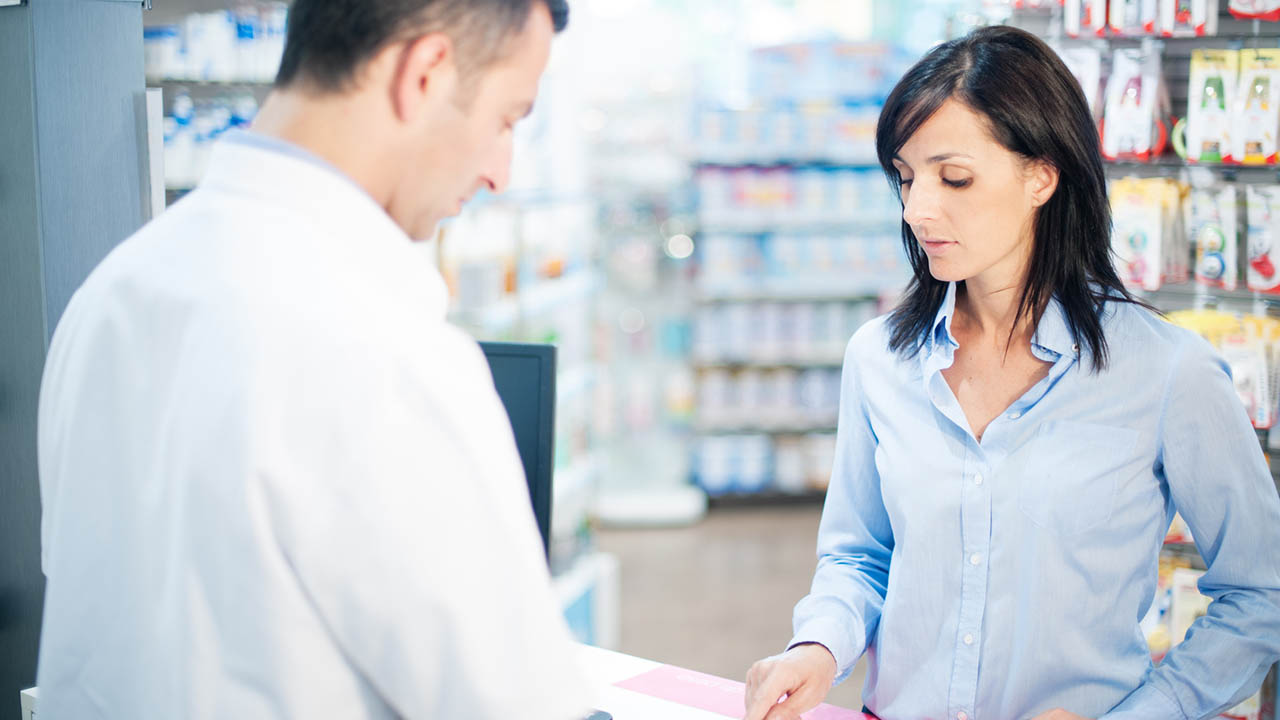 Woman discusses prescriptions with pharmacist