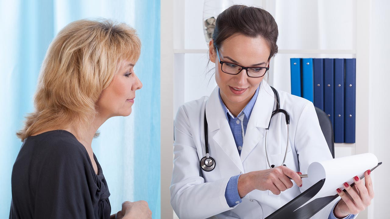 Doctor discusses notes with patient