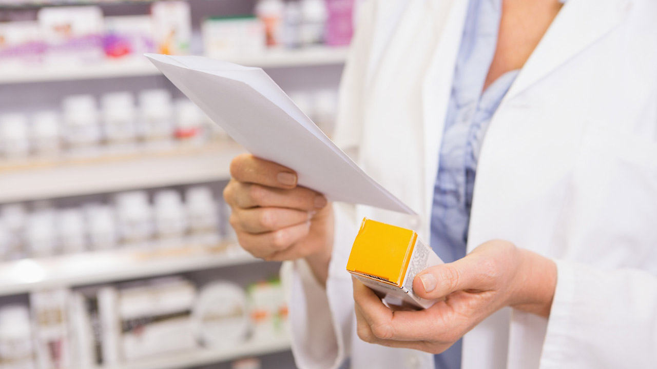 Pharmacist looks at prescription and medication
