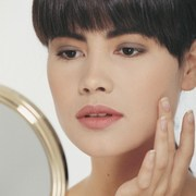 woman-looking-at-clean-skin-in-the-mirror