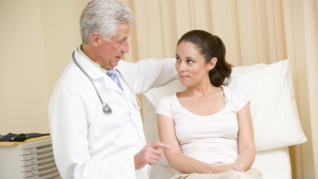 Woman embarrassed talking to doctor